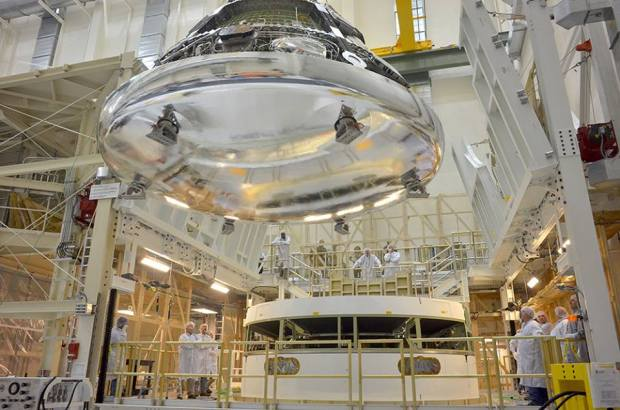 Orion, seen here with its heat shield installed, being maneuvered for stacking on the spacecraft's service module at KSC earlier this month. (Credit: NASA)