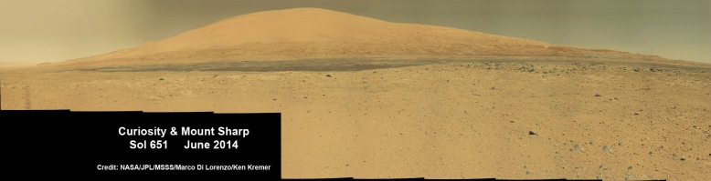 Curiosity rover panorama of Mount Sharp captured on June 6, 2014 (Sol 651) during traverse inside Gale Crater. Note rover wheel tracks at left. She will eventually ascend the mountain at the 'Murray Buttes' at right later this year. Assembled from Mastcam color camera raw images and stitched by Marco Di Lorenzo and Ken Kremer. Credit: NASA/JPL/MSSS/Marco Di Lorenzo