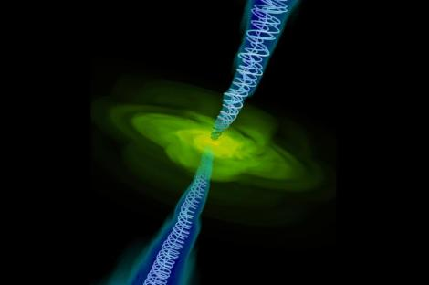 This is a computer simulation of gas (in yellow) falling into a black hole (too small to be seen). Twin jets are also shown with magnetic field lines. Credit: Alexander Tchekhovskoy, Berkeley Lab