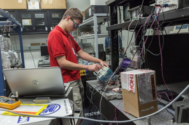 NASA Goddard intern Robert Buttles adjusts equipment used for the eLISA mission, which will test for vibrations that could reveal subtle changes in gravity. Image (Credit: NASA Goddard/Kristen Basham)