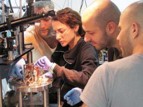 This image depicts from left to right Serge Rosenblum, Yulia Lovsky, Orel Bechler and Itay Shomroni.  At the center of the photonic router is a single atom that routes photons  in different directions. (Credit: Weizmann Institute of Science)