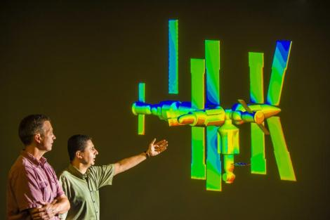 Sandia National Laboratories researchers Steve Plimpton, left, and Michael Gallis look at a projection of a model of the Russian MIR space station, which fell out of orbit several years ago and disintegrated, with the remains ending up at the bottom of the Indian Ocean. Using Sandia's 3-D code SPARTA, the calculation is simulating an instance of the process of de-orbiting. (Credit: Randy Montoya)