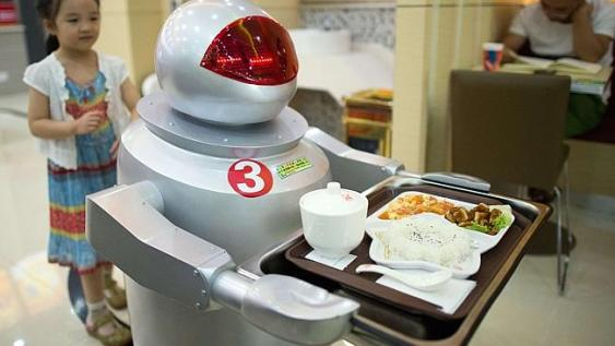 A robot carries food to customers in a restaurant in Kunshan, China. Photo: Johannes Eisele. (Credit: AFP)