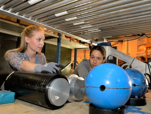 Los Alamos National Laboratory postdoc Elena Guardincerri, right, and undergraduate research assistant Shelby Fellows prepare a lead hemisphere inside a muon tomography machine. (Credit: Los Alamos National Laboratory)