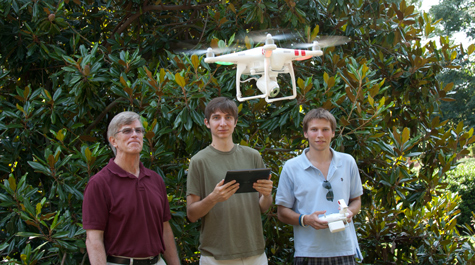 Reed Beverstock (right) pilots the physics department quadcopter while Daniel Duane (center) monitors the video feed on a computer tablet while Professor of Physics Bill Cooke looks on. They're using the device to create video tutorials as part of a Creative Adaptation initiative. (Credit: Joseph McClain)