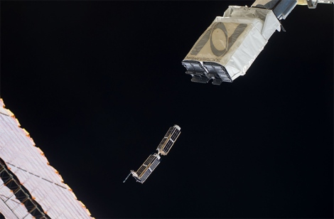 In the grasp of the Japanese robotic arm, NanoRack's CubeSat deployer releases a pair of miniature satellites last month. (Credit: NASA)