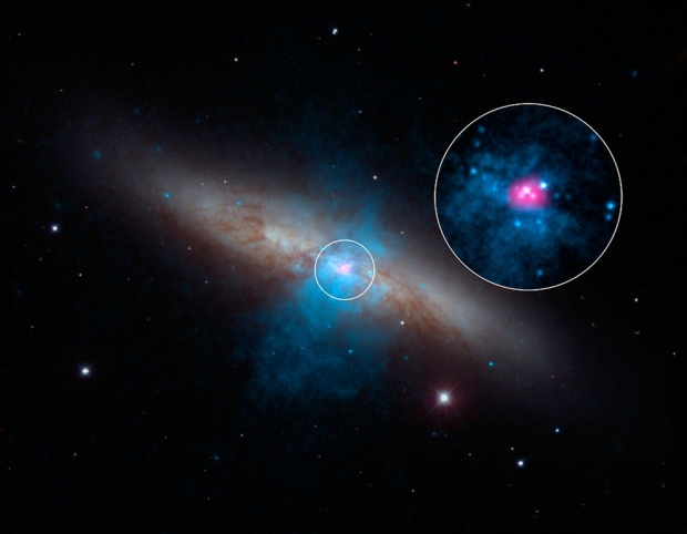 """Astronomers have found a pulsating dead star beaming with the energy of about 10 million Suns, which is the brightest pulsar ever recorded..  A rare and mighty pulsar (pink) can be seen at the center of galaxy M82 in this new multi-wavelength portrait. NASA's NuSTAR mission discovered the """"pulse"""" of the pulsar — a type of dead star — using is high-energy X-ray vision."""