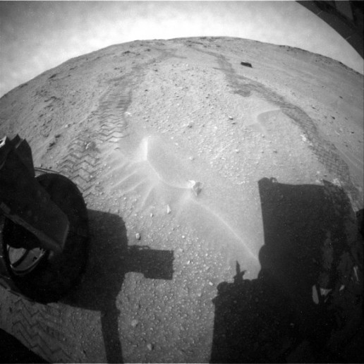 After a couple of years of racing towards Mount Sharp (Aeolis Mons), now it's time for the Curiosity rover to get a better look at its Martian surroundings. Rover tracks and Martian sand as seen from the rear hazcam of NASA's Curiosity rover. (Credit: NASA/JPL-Caltech)